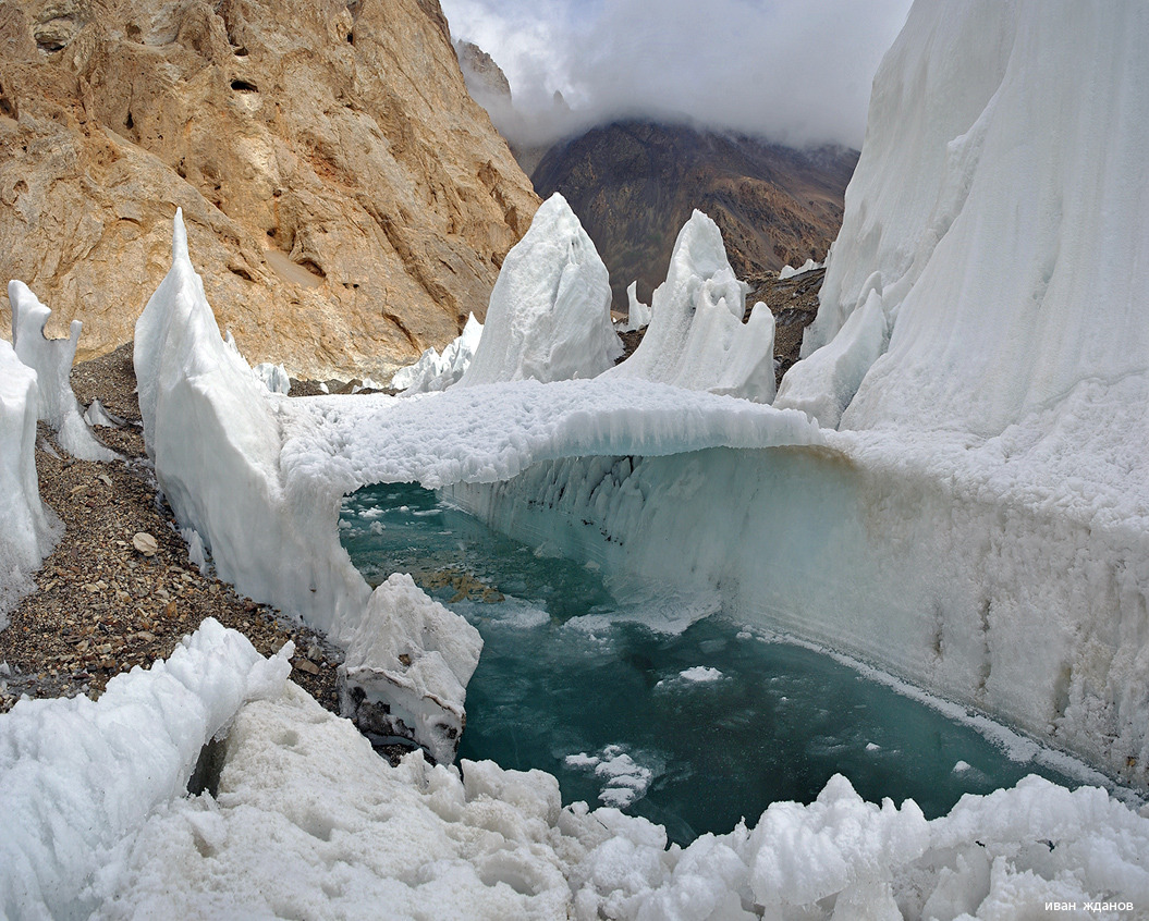 Melting river and frozen bridge in one of Central Asia glaciers